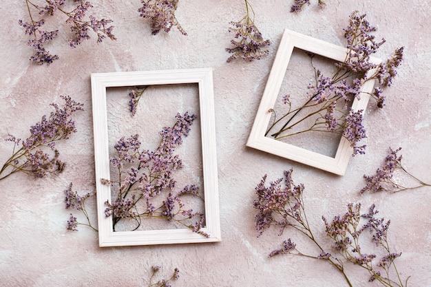 Fiori viola secchi in due cornici di legno bianche e accanto a loro su uno sfondo strutturato. cartolina d'epoca di auguri romantico. vista dall'alto
