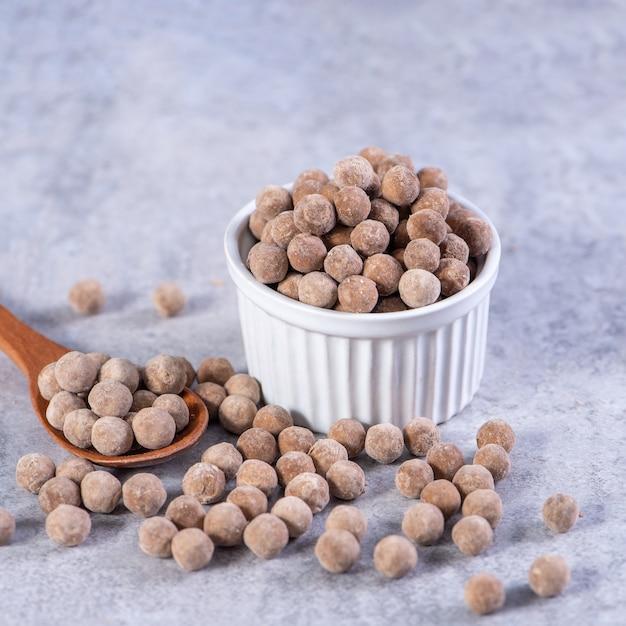 Perle di tapioca marroni crude asciutte isolate su fondo di cemento grigio cemento, primo piano, ingrediente per preparare il tè al latte di tapioca boba boba.