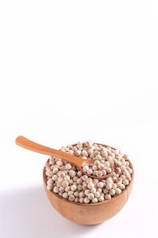 Perle di tapioca marroni crude asciutte in una ciotola di legno con cucchiaio isolato su sfondo bianco, primo piano, ingrediente per preparare il tè al latte di bubble boba.