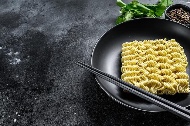 Pasta secca, cruda a cottura rapida, spaghetti istantanei. sfondo nero. vista dall'alto. copia spazio.