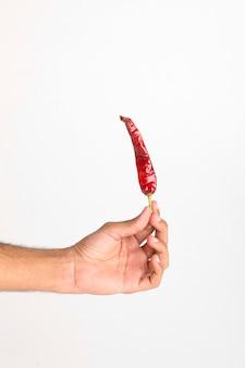 Peperoncino rosso secco che tiene in mano sulla superficie bianca