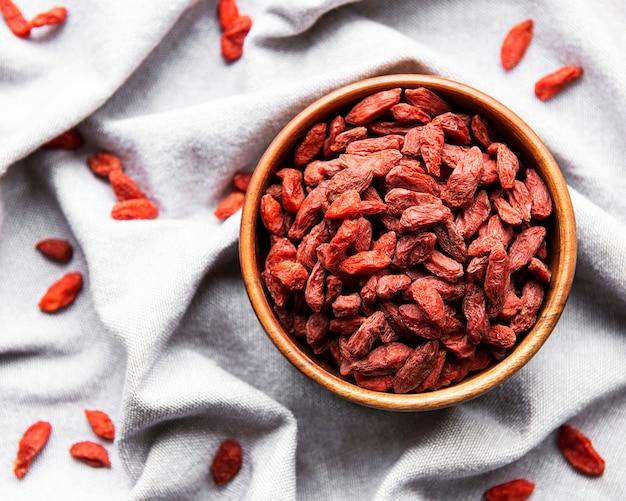 Bacche di goji rosse secche per una dieta sana su una superficie di tessuto