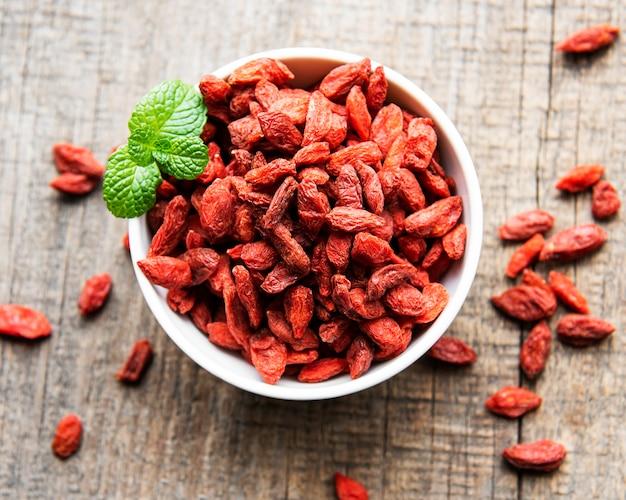 Bacche di goji rosse secche per una dieta sana su un vecchio fondo di legno
