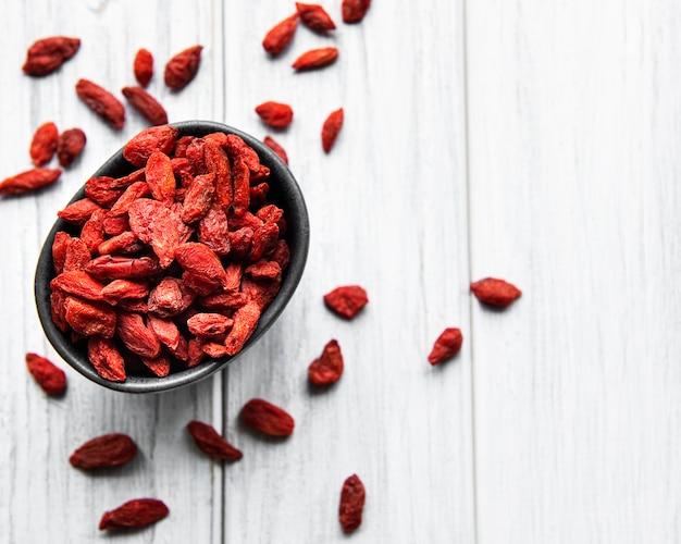 Bacche di goji rosse secche per una dieta sana su un fondo di legno vecchio
