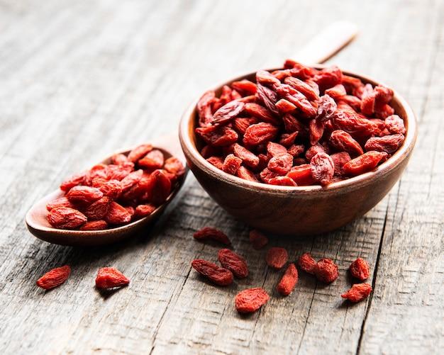 Bacche di goji rosse secche per una dieta sana su una vecchia superficie di legno
