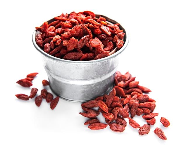 Bacche di goji rosse secche per una dieta sana su una superficie bianca