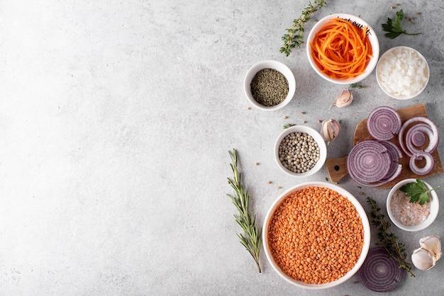 Asciugare le lenticchie rosse in una ciotola bianca con cipolle e spezie