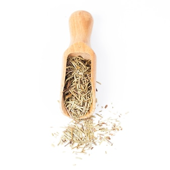 Erba di rosmarino secco in paletta di legno su sfondo bianco