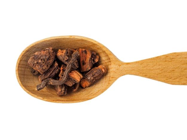 Radice di rubia secca in un cucchiaio di legno isolato su uno sfondo bianco