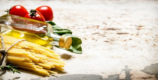 Spaghetti secchi con olio d'oliva, pomodori ed erbe aromatiche. su fondo rustico. spazio libero per il testo.