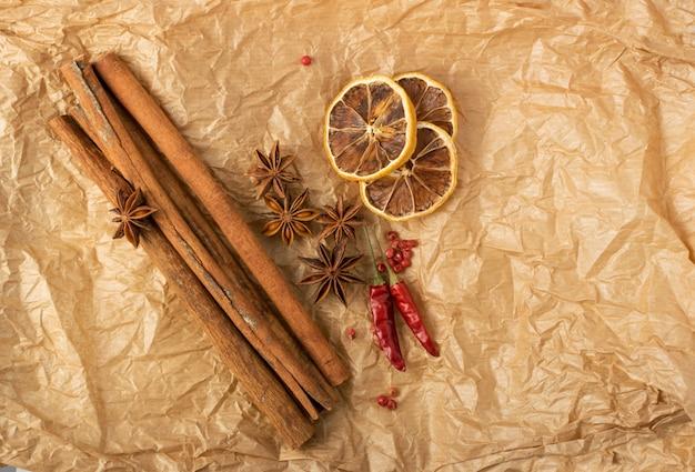 Spezie secche per vin brulè con agrumi a fette disidratati su carta kraft vintage