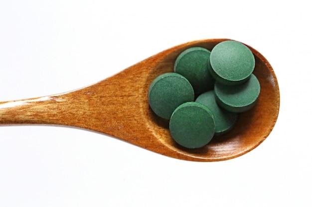 Spirulina secca in compresse in un cucchiaio di legno