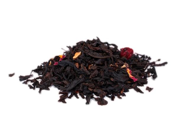 Foglie di tè secche con pezzi di frutta e petali di fiori isolati su un bianco