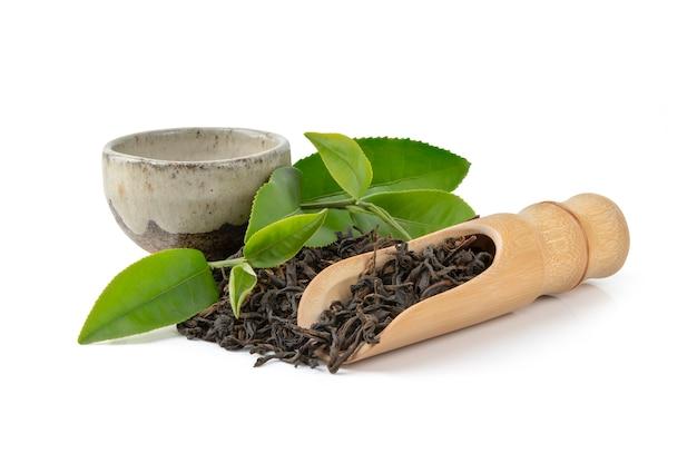 Tè secco in cucchiai di legno con foglie verdi e tazza