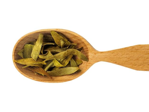 Petali di viscum secchi in un cucchiaio di legno isolato su uno sfondo bianco