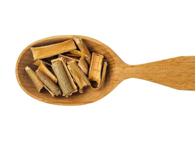 Corteccia di salice secco in un cucchiaio di legno isolato su uno sfondo bianco