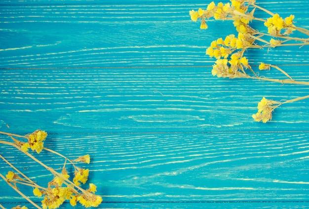 Fiori gialli asciutti che formano una struttura su un fondo di legno d'annata, retro stile