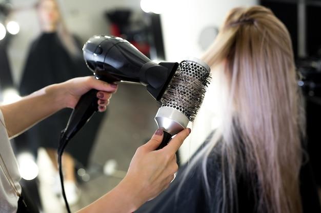 Asciugare i capelli biondi lunghi con asciugacapelli e spazzola tonda