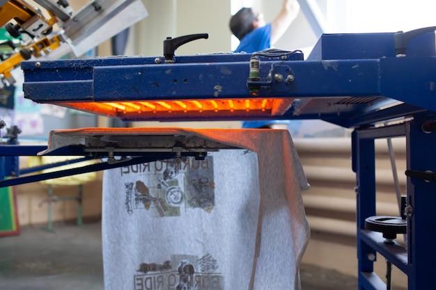 Forno di asciugatura per il processo di stampa serigrafica serigrafica presso la fabbrica di abbigliamento.