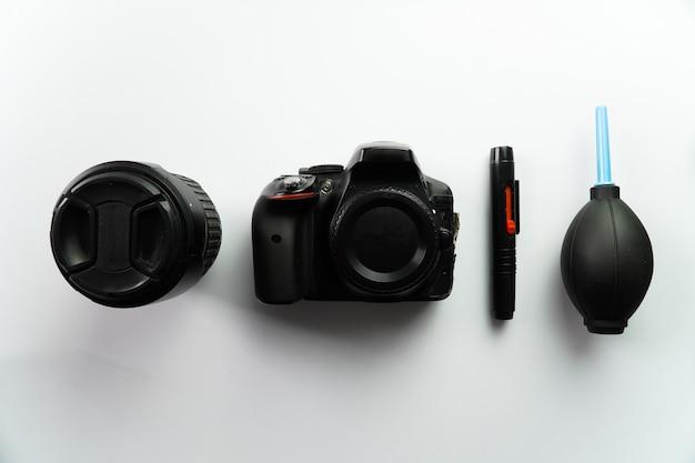 Fotocamera dslr con obiettivo e kit di pulizia su sfondo bianco