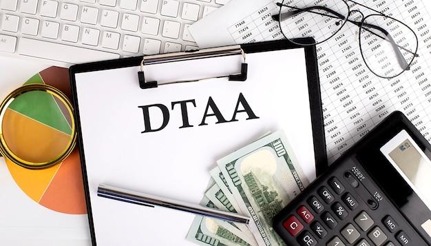 Accordo di evitazione della doppia tassazione dtaa sul tavolo della scrivania dell'ufficio con tastiera, dollari, calcolatrice, forniture, grafico di analisi sulla superficie bianca