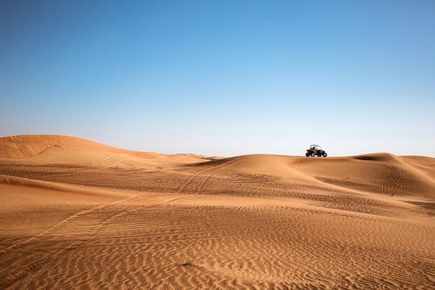 Paesaggio minimalista sabbioso del deserto di dubai con un quad buggy lontano