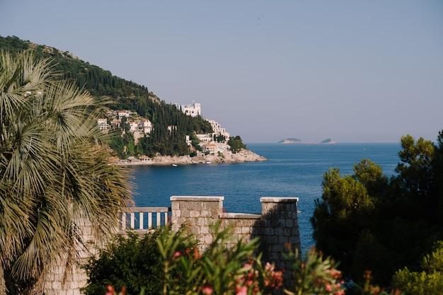 Vista della costa di dubrovnik da una villa in riva al mare e isole del mare adriatico attraverso le palme