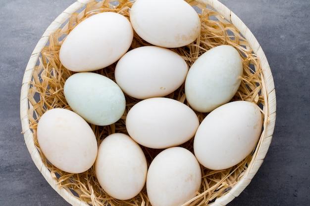 Uova di anatra su una superficie grigia della gabbia.