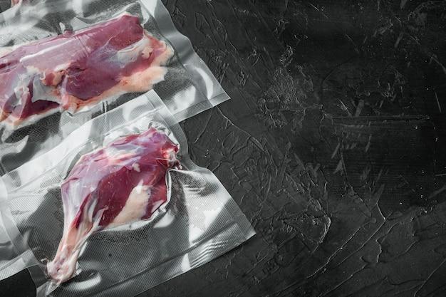 Carne d'anatra, cruda stagionata appena macellata dalla fattoria biologica preparata per l'aspirapolvere e il set per fumare, su sfondo di pietra nera, con copyspace e spazio per il testo