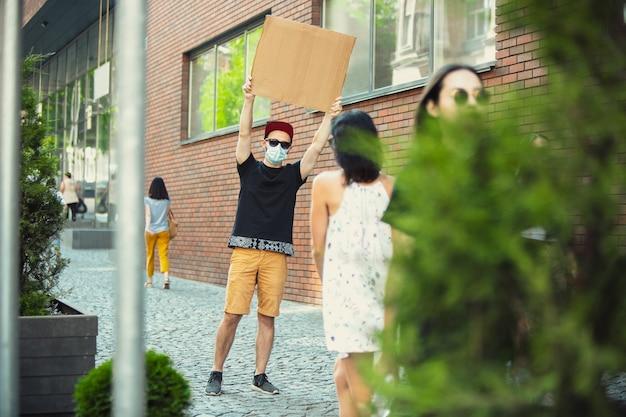 Amico con il segno: l'uomo sta protestando contro le cose che lo infastidiscono