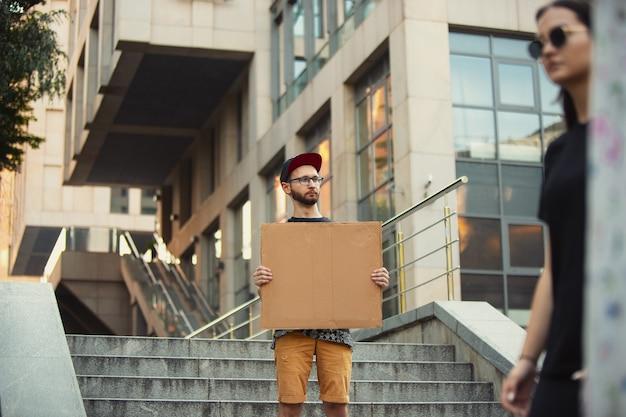 Amico con il segno, l'uomo sta protestando contro le cose che lo infastidiscono