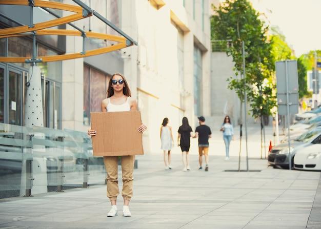 Amico con il segno - la donna sta in piedi a protestare contro le cose che la infastidiscono