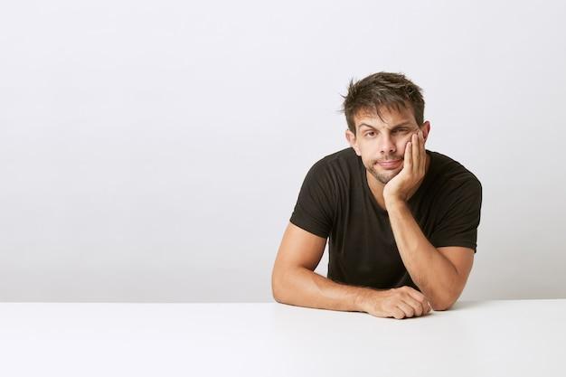 Uomo giovane bello opaco, con i gomiti che si appoggiano sulla scrivania bianca e la testa appoggiata sulle mani. isolato sulla scrivania bianca. indossare una maglietta nera.
