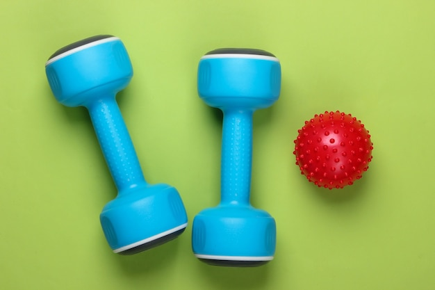 Manubrio con palla da massaggio sul verde. fitness, concetto di stile di vita sano