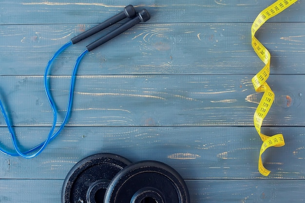 Manubri con taccuino, bilance, corda per saltare e bottiglia d'acqua su legno