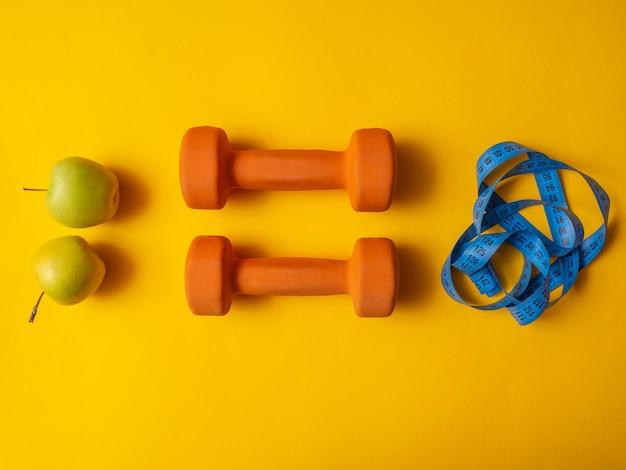 Manubri per fitness, mele e nastro di misurazione su uno sfondo giallo. concetto di perdita di peso. flatlay, copyspace.