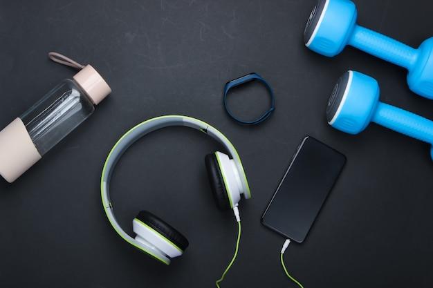 Manubri, cuffie con smartphone, braccialetto intelligente, bottiglia d'acqua su superficie nera