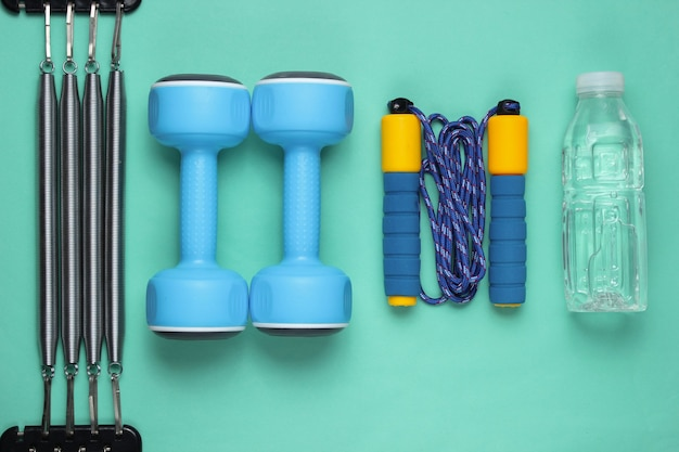 Manubri, corda per saltare, bottiglia d'acqua, espansore. attrezzature sportive su sfondo blu. vista dall'alto