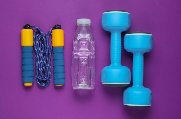 Manubri, corda per saltare, bottiglia d'acqua. attrezzature sportive su sfondo viola.