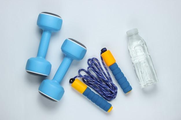 Manubri, corda per saltare, bottiglia d'acqua. attrezzature sportive su sfondo bianco. vista dall'alto