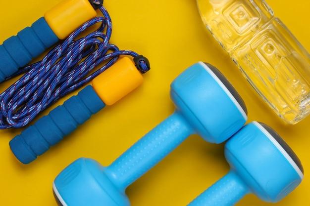 Manubri, corda per saltare, bottiglia d'acqua. attrezzature sportive su sfondo giallo. copia spazio. vista dall'alto