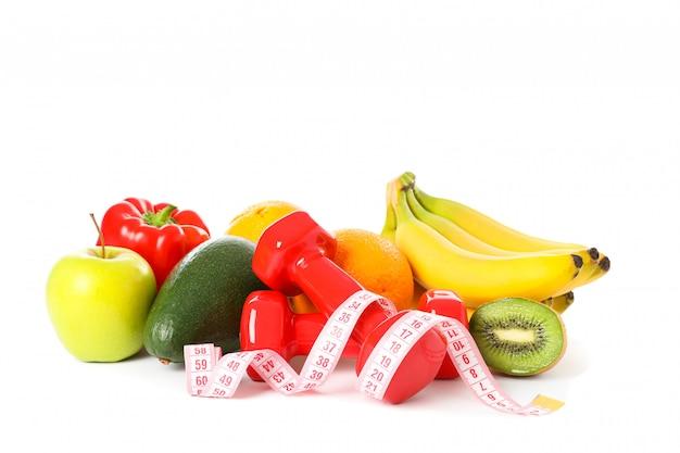 Dumbbells, nastro di misurazione e frutti isolati su bianco