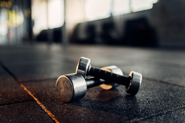 Manubri sulla vista del primo piano del pavimento in gomma, fitness club