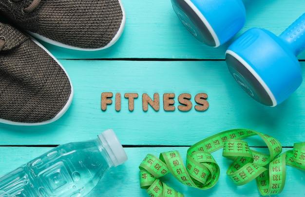 Manubri, righello, bottiglia d'acqua, scarpe da ginnastica su superficie di legno blu con la parola fitness