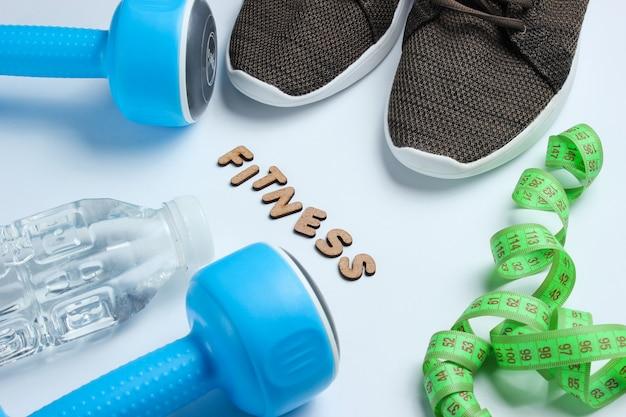 Manubri, righello, bottiglia d'acqua, scarpe da ginnastica su superficie grigia con la parola fitness