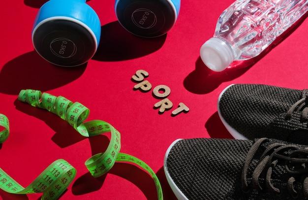 Manubri, righello, bottiglia d'acqua, scarpe da ginnastica sulla superficie rossa con la parola sport
