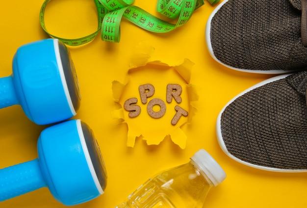 Manubri, righello, bottiglia d'acqua, scarpe da ginnastica sulla superficie gialla con la parola sport nel buco strappato