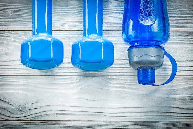 Bottiglia d'acqua con manubri sul concetto di formazione sportiva tavola di legno