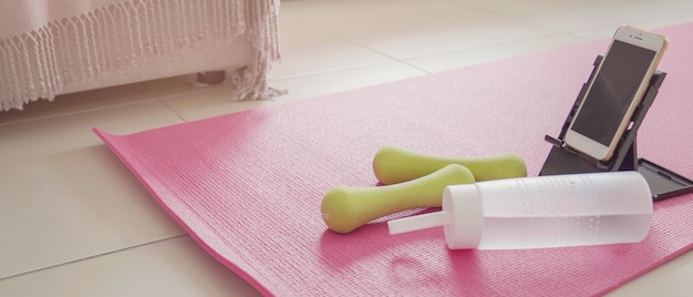 Manubri, bottiglie d'acqua e smartphone sul tappetino rosa, allenamento in casa, esercitazione di video in streaming online, concetto di distanza sociale