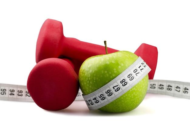 Manubri con nastro di misurazione e mela per il concetto di dieta sullo sfondo